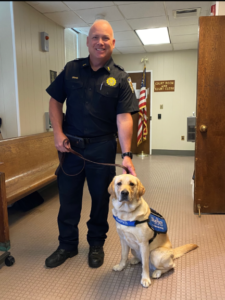 Rye PD Lieutenant Scott Craig with a service dog from Blue Path
