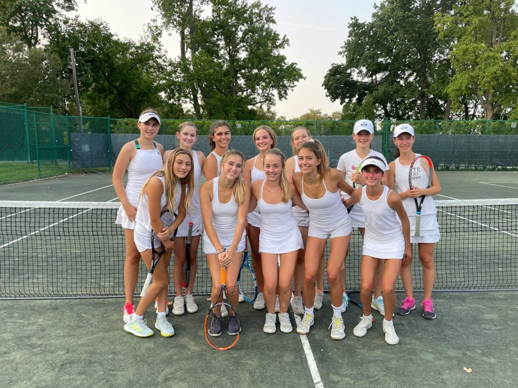 (PHOTO: The Rye Girls Varsity Tennis # 1 team poses for a photo in their tennis whites after practice at Manursing Island Club.)