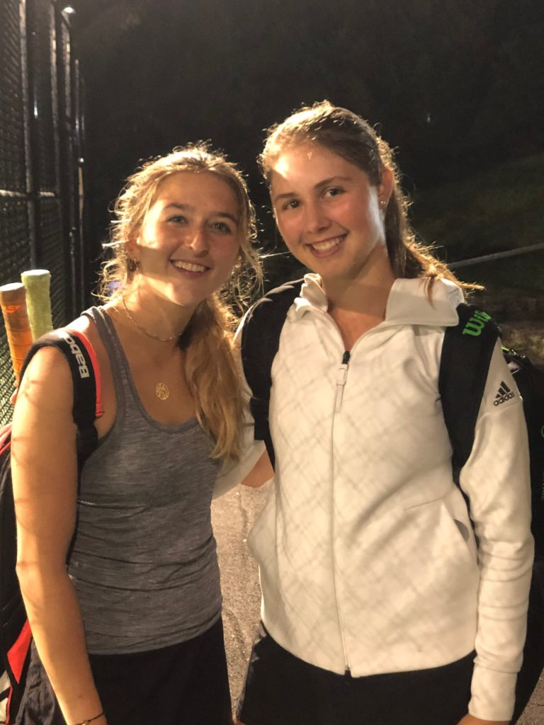(PHOTO: Rye's #1 seeded doubles team of senior captains Juliette Stone and Charlotte Ausfahl smile in celebration following their semifinal victory at the Sectional tournament qualifying them for States.)